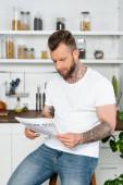 junger tätowierter Mann in weißem T-Shirt liest Zeitung in Küche
