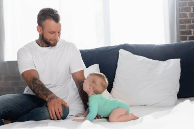 Young tattooed man in white t-shirt and jeans sitting near infant son crawling on bed in baby romper stock vector