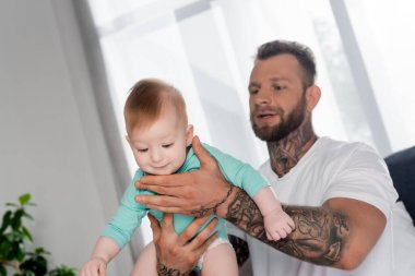 Selective focus of bearded tattooed man holding baby boy in bedroom stock vector