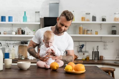 Young father near infant child holding spoon near mouth while sitting on kitchen table during breakfast stock vector
