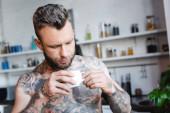 fiatal tetovált férfi kezében csésze kávét a konyhában