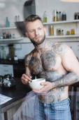 bez košile vytetovaný muž dívá pryč, zatímco drží misku se snídaní v kuchyni