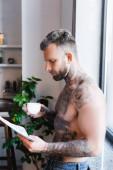 Seitenansicht eines hemdlosen tätowierten Mannes, der Zeitung liest, während er eine Kaffeetasse in der Küche hält