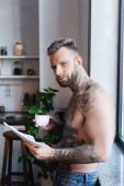 mladý tetovaný muž drží šálek kávy a novin při snídani v kuchyni