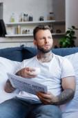 selektivní zaměření vousatého tetovaného muže držícího šálek kávy a noviny při sezení v posteli