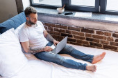 Photo tattooed freelancer in jeans and white t-shirt using laptop on bed near newspaper, smartphone and bowl on windowsill
