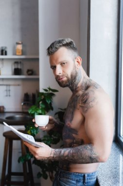 Young tattooed man holding cup of coffee and newspaper during breakfast in kitchen stock vector