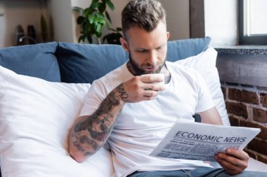 Bearded tattooed man drinking coffee and reading newspaper in bedroom stock vector
