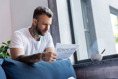 Young tattooed man reading newspaper near window at home stock vector