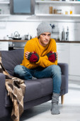 freezing man in warm hat and fingerless gloves hugging himself while sitting on sofa in cold kitchen