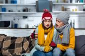 fiatal férfi meleg kalap és sál ölelés fagyasztó barátnő, miközben ül a hideg konyhában