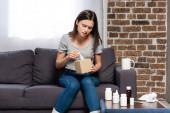 Kranke Frau nimmt Papierserviette, während sie neben Tasse mit warmem Getränk und Nachttisch mit Medikamenten sitzt