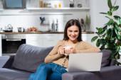 Aufgeregter Freiberufler blickt auf Laptop, während er in der Küche auf dem Sofa mit einer Tasse warmen Tee sitzt