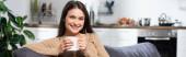 horizontální koncept potěšené ženy při pohledu na kameru při sezení na gauči v kuchyni s šálkem teplého nápoje