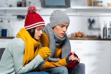 Young couple in warm hats, scarfs and gloves sitting with clenched hands while freezing in cold kitchen stock vector