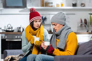 Freezing couple in knitted hats, scarfs and gloves holding cups of warming beverage in cold kitchen stock vector