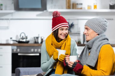 Joyful couple in warm hats, scarfs and gloves looking at each other while holding cups of warming beverage in kitchen stock vector