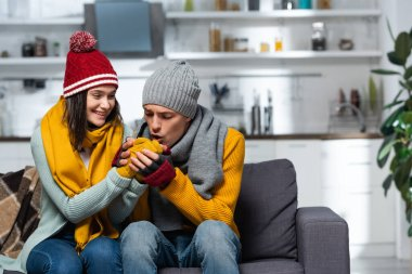 Young man in knitted hat, scarf and gloves warming hands of freezing girlfriend stock vector