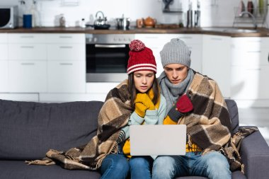 Freezing couple in warm hats and gloves watching movie on laptop while sitting on sofa under plaid blanket stock vector