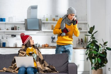 Cold woman in warm hat and gloves sitting on sofa under plaid blanket while worried boyfriend talking on smartphone stock vector