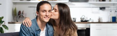 Panoramic orientation of brunette woman kissing pleased boyfriend looking at camera in kitchen stock vector