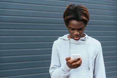 Upset african american teenager using smartphone outdoors stock vector