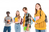 Smiling multicultural teenagers with backpacks and books showing like isolated on white