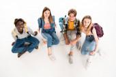 Általános kilátás többnemzetiségű tinédzserek hátizsákos mosolygós kamera fehér háttér
