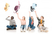 Positive multiethnic teenagers throwing backpacks while sitting on white background