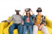 Mosolygó multikulturális tinédzserek vr headsetek ül sárga kanapén elszigetelt fehér