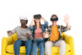 Vidám, többnemzetiségű tinédzserek vr headsettel sárga kanapén, fehér alapon izolálva