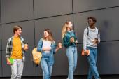 Pozitív többnemzetiségű tinédzserek hátizsákkal és kávéval, akik az épület közelében sétálnak