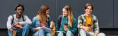 Panoramatický záběr multietnické teenagery s kávou jít a notebooky mluvit v blízkosti budovy