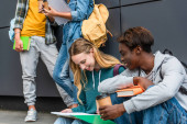 Selective focus of smiling african american teenager with coffee to go and book sitting near friend with notebook on sidewalk near building