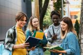 Szelektív fókusz a pozitív többnemzetiségű tinédzserek nézi könyvet közelében fa szabadban