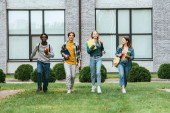 Selective focus of cheerful multiethnic teenagers with notebooks and backpacks walking on grass outdoors