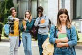 Selektivní zaměření smutného teenagera s knihou a batohem stojící poblíž multietnických školáků ukazujících prstem ven
