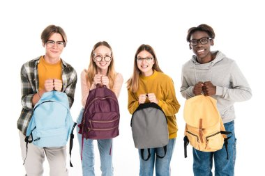 Smiling multicultural teenagers holding backpacks and looking at camera isolated on white stock vector