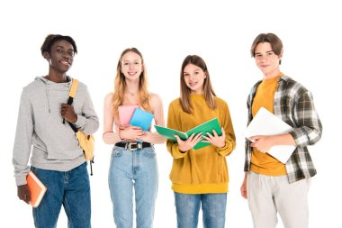 Multiethnic teenagers with books and laptop smiling at camera isolated on white stock vector