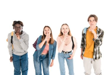 Smiling multiethnic teenagers with backpacks showing shh gesture isolated on white stock vector