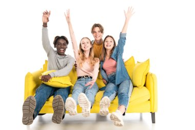 Positive multiethnic teenagers waving hands at camera while sitting on couch on white background stock vector