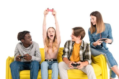 KYIV, UKRAINE - AUGUST 21, 2020: Cheerful multicultural teenagers playing video game on yellow sofa isolated on white stock vector