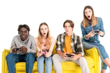 KYIV, UKRAINE - AUGUST 21, 2020: Excited multicultural friends holding joysticks on yellow couch isolated on white stock vector