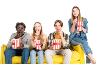 Multicultural friends smiling while eating popcorn on yellow couch isolated on white stock vector