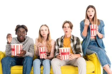 Shocked multicultural friends holding buckets of popcorn on yellow sofa isolated on white stock vector