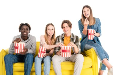 Smiling multicultural friends holding buckets of popcorn on yellow couch isolated on white stock vector
