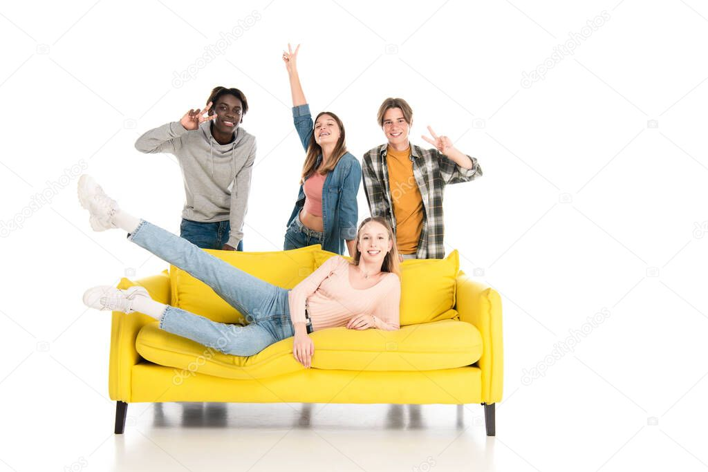 Cheerful multiethnic teenagers showing peace gesture on yellow couch on white background stock vector