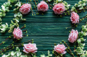 top view of wooden green background with blossoming branches, roses