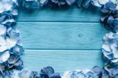 vrchní pohled na dřevěné modré pozadí s květinovým rámem