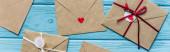 pohled shora na dřevěné modré pozadí s obálkami a srdcem, panoramatický záběr